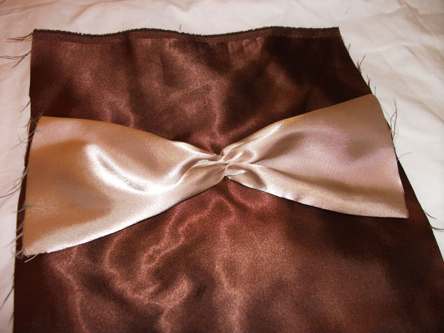 securing the bow in the center of the top pillow piece